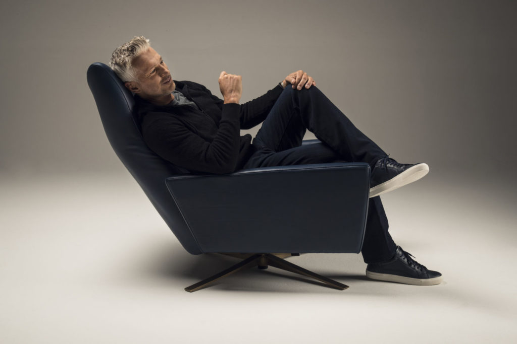 Man sitting in a Comfort Air Stratus Chair with legs crossed. Side view.